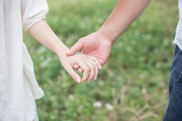30代のカップルがお互いの手を取りながら結婚観について話している様子。