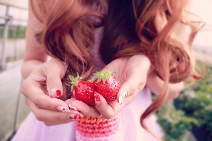 男性に可愛いイチゴを差し出している女性の画像。