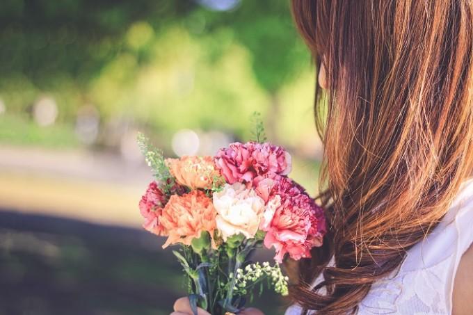 年上女性が年下男性のことを考えて花を持っている様子
