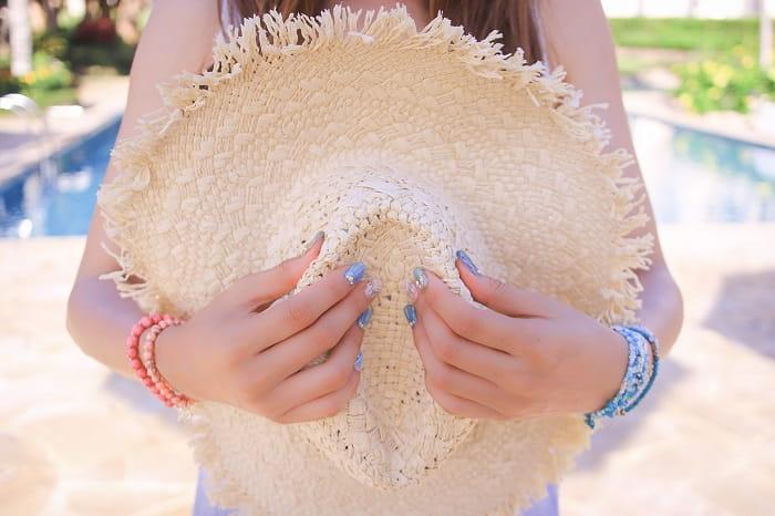 好きな人と上手く話せない女性が麦わら帽子を胸に抱えている