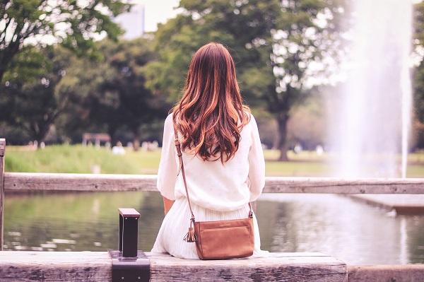 一生彼氏ができないと不安な女性が公園のベンチに一人で座っている様子。