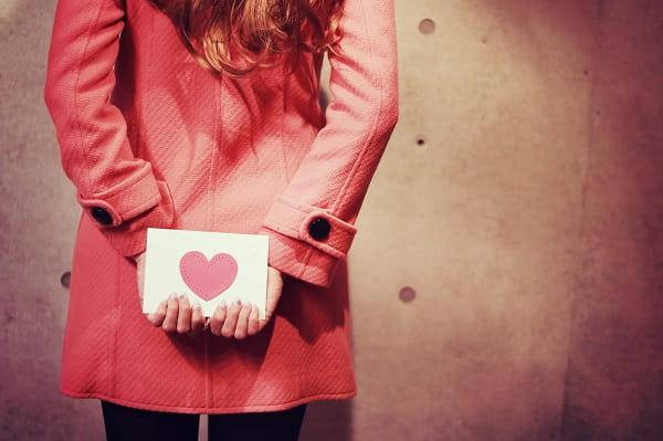 好きな人のことを見つめる女性。後ろの手紙は恋愛感情を隠しているイメージ。