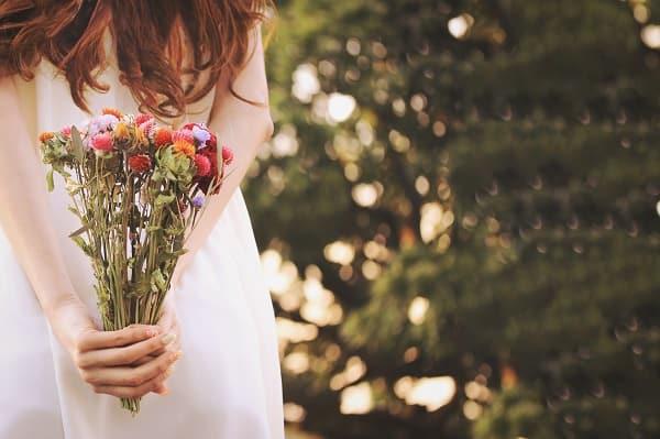 聞き上手な男性を好きになった女性の画像。気持ちを込めた花束を持っている。