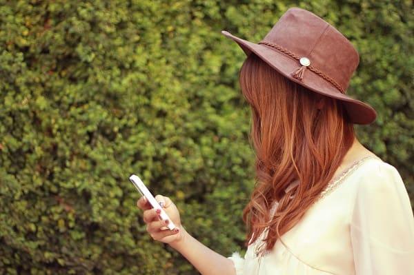 好きな人から久しぶりにLINEが気女性。携帯を見つめている。