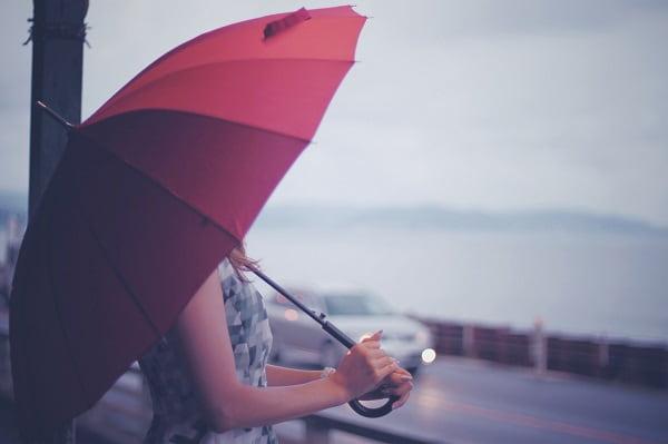 男性からモテる「隙がある女性」が傘をさして海を眺めている様子。
